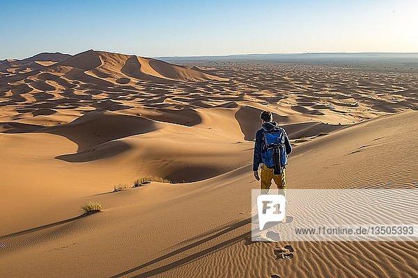 Young man walks on a sand dune  dune landscape Erg Chebbi  Merzouga  Sahara  Morocco  Africa