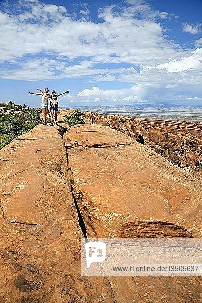 Wanderer balancieren auf einem Sandsteinfelsen im Devil's Garden  Arches-Nationalpark  bei Moab  Utah  USA  Nordamerika