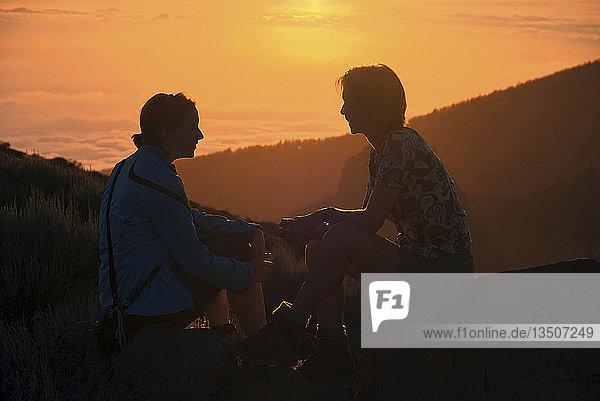 Mutter und Kind bei Sonnenuntergang im Teide Nationalpark mit Blick auf das Wolkenmeer vor La Palma  Teneriffa  Kanarische Insel  Spanien  Europa
