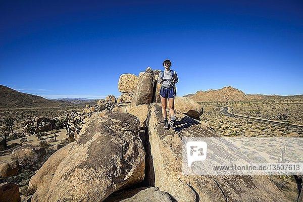 Junge Frau auf Boulder  Gewaltige Granitfelsen  Quail Springs Picnic Area  Joshua-Tree-Nationalpark  Desert Center  Kalifornien  USA  Nordamerika