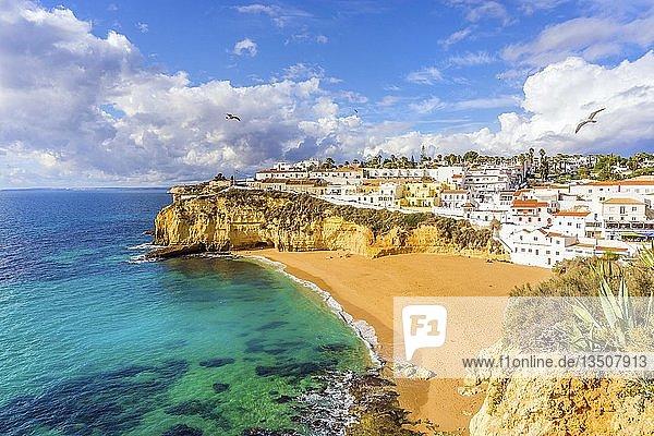 Wide sandy beach  white houses  cloudy sky with seagulls  Carvoeiro  Algarve  Portugal  Europe