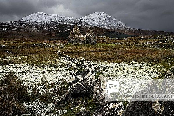 Felsenreihe mit weißen Kappen und Haus Ruine in Highland Landschaft mit verschneiten Cullin Bergen im Hintergrund  Broadford  Isle of Skye  Schottland  Großbritannien  Europa