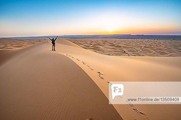Junger Mann streckt die Arme in die Luft  Sanddüne bei Sonnenaufgang  Erg Chebbi  Merzouga  Sahara  Marokko  Afrika