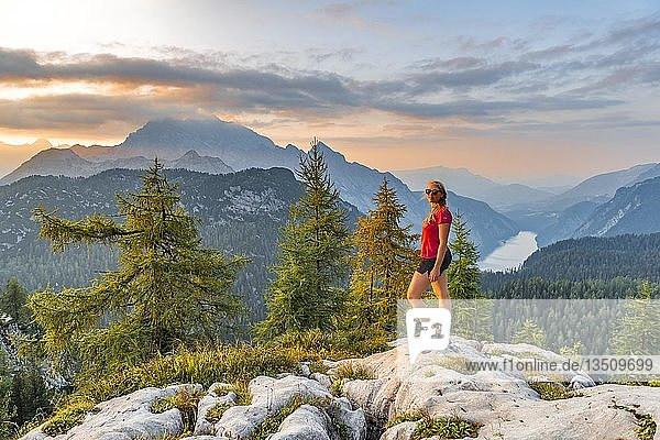 Wanderin blickt in die Kamera  Ausblick über den Königssee von dem Feldkogel  links Watzmann Südspitze und Watzmann-Kinder  rechts Funtenseetauern  Sonnenuntergang  Nationalpark Berchtesgaden  Berchtesgadener Land  Oberbayern  Bayern  Deutschland  Europa