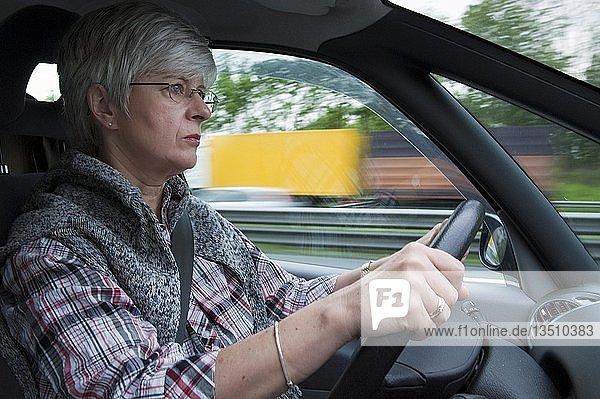 Frau  50+  am Steuer eines PKW auf der Autobahn