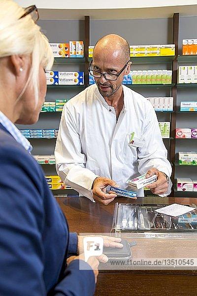 Apotheke  Apotheker berät eine Kundin  die ein Medikament auf Rezept abholt  Deutschland  Europa