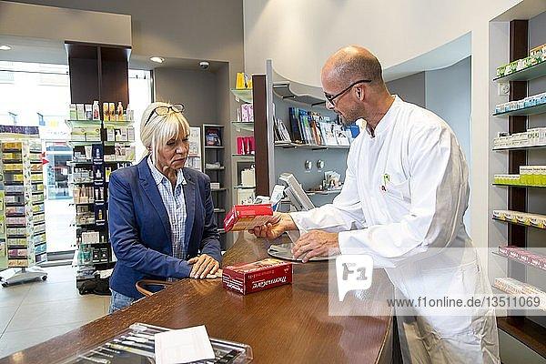 Apotheke  Apotheker berät eine Kundin  die ein Medikament kaufen möchte  Deutschland  Europa