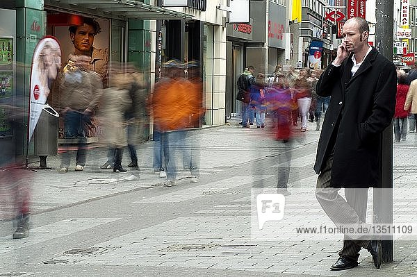 Young man standing in a pedestrian zone and speaking on his mobile phone