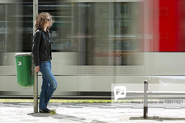 Junge Frau steht an einer Straßenbahnhaltestelle