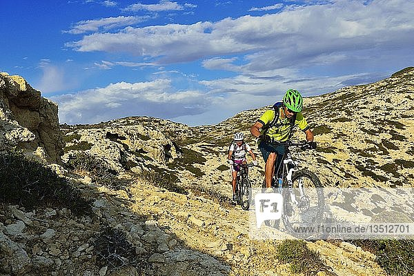 Zwei Mountainbiker radeln in felsigem Gelände  Red Beach  Matala  Kreta  Griechenland  Europa