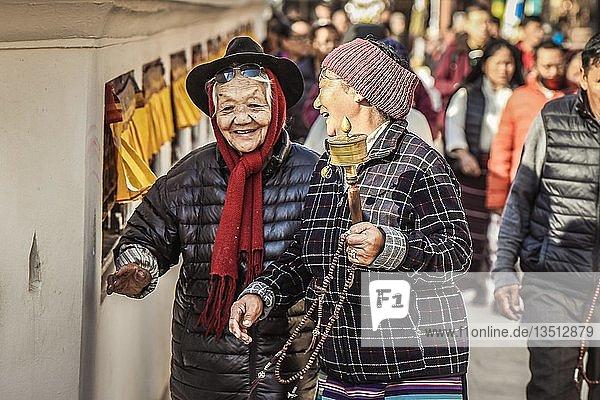 Lachende Tibeterinnen mit Gebetsmühle  Boudhanath Stupa  Boudha  Tibetischer Buddhismus  Kathmandu  Nepal  Asien