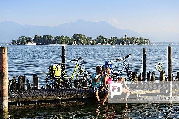 Radfahrer bei Rast auf Bootssteg  Gstadt am Chiemsee  hinten Insel Frauenchiemsee  Chiemgau  Oberbayern  Bayern  Deutschland  Europa