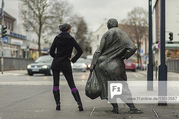 Junge Frau neben Bronzestatue in der Fußgängerzone  Grevenbroich  Nordrhein-Westfalen  Deutschland  Europa