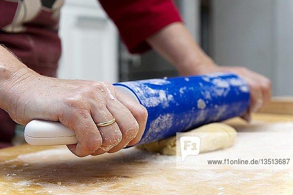 Hände führen Nudelholz und walzen Teig aus