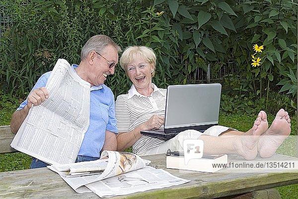 Seniorenpaar mit Laptop und Zeitung