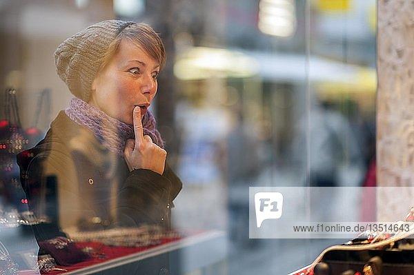 Junge Frau betrachtet das Schaufenster eines Juweliers  Grevenbroich  Nordrhein-Westfalen  Deutschland  Europa
