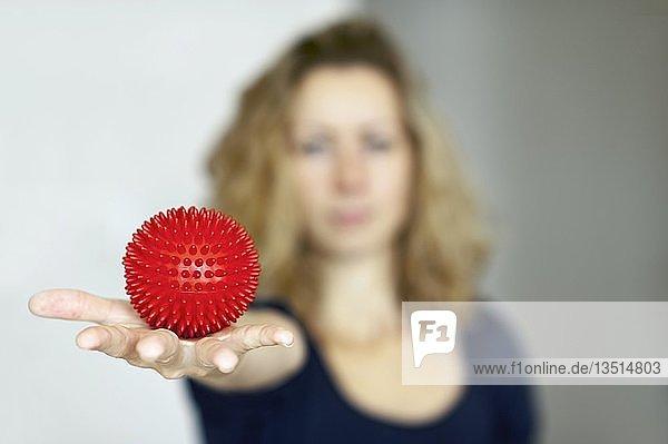 Junge Frau mit Massageigel in der ausgestreckten Hand