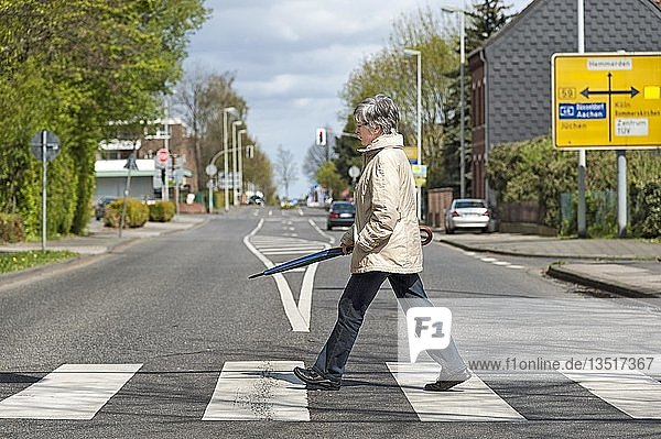 Eine Frau überquert die Straße auf einem Zebrastreifen  Grevenbroich  Nordrhein-Westfalen  Deutschland  Europa