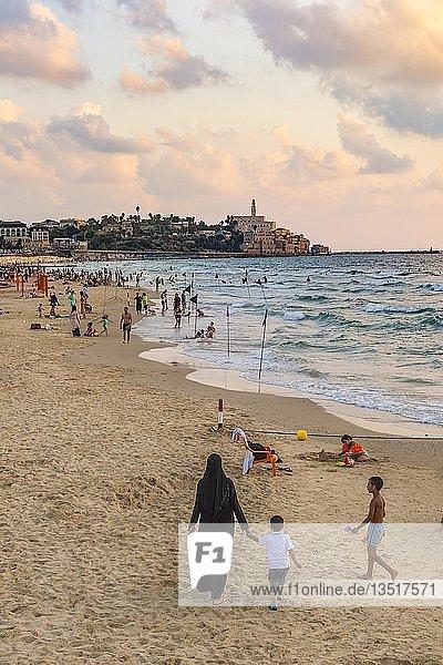 Einheimische am Strand  Frau mit Burka und kleinem Kind  Abendstimmung  Alma Beach  hinten Tel-Aviv-Jaffa  Altstadt  Tel Aviv  Israel  Asien