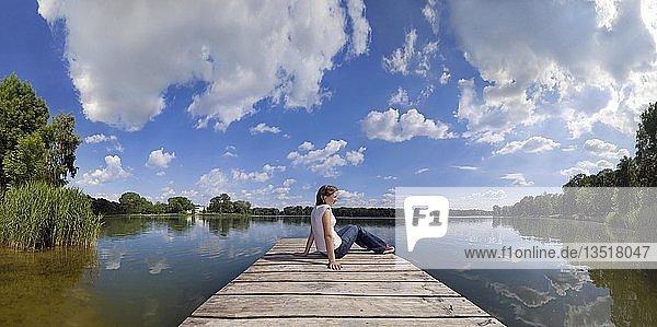 Mädchen relaxt auf einem Badesteg eines Baggersees mit sich darin spiegelndem Wolkenhimmel  Ingolstadt  Bayern  Deutschland  Europa