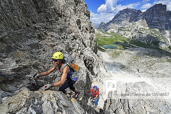 Hikers on the via ferrata  ascent to the Paternkofel  in the back Lake Bödensee  Sexten Dolomites  Alta Pusteria  South Tyrol  Italy  Europe