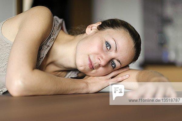 Junge Frau legt den Kopf auf den Arm