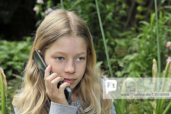 9jähriges Mädchen telefoniert mit Handy im Garten