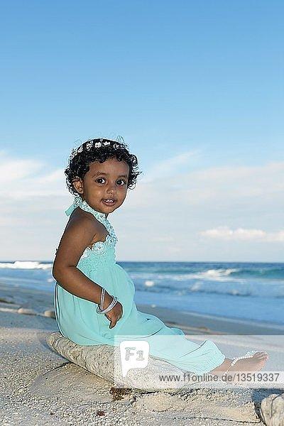 Kleines maledivisches Mädchen am Strand  auf Stein sitzend  Fuvahmulah Island  Indischer Ozean  Malediven  Asien