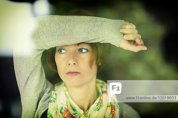 Junge Frau schaut nachdenklich durch eine Fensterscheibe  Grevenbroich  Rheinland  Nordrhein-Westfalen  Deutschland  Europa