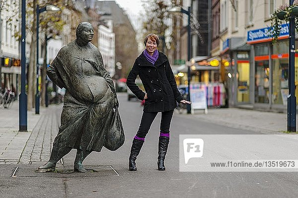 Junge Frau neben Bronzefigur in der Fußgängerzone  Grevenbroich  Nordrhein-Westfalen  Deutschland  Europa