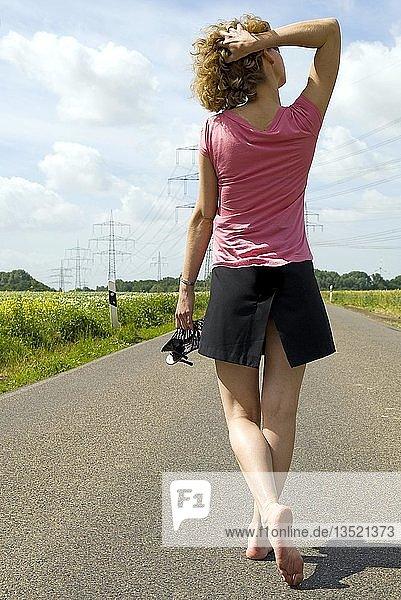 Junge Frau geht barfuß auf einer Landstraße