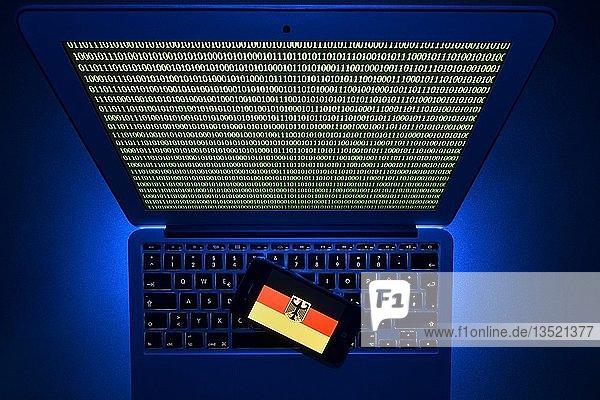 Smartphone mit deutscher Flagge mit Bundesadler auf Computertastatur  Symbolbild Cybercrime  Hackerangriff auf deutsche Behörden  Baden-Württemberg  Deutschland  Europa