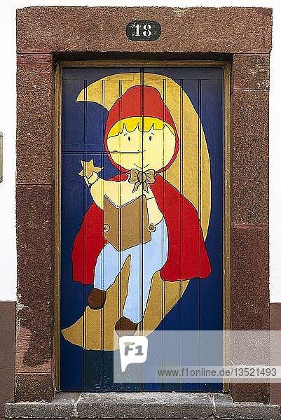 Kind mit Buch und Stern sitzt im Halbmond  kunstvoll bemalte Haustür  Straßenkunst  Funchal  Madeira  Portugal  Europa