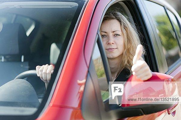 Junge Frau schaut aus dem Fenster eines PKW  zeigt Daumen hoch
