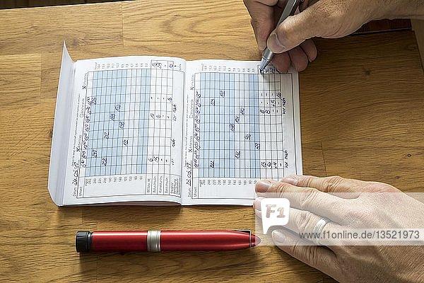 Diabetics keep his blood sugar diary  record blood sugar values  Germany  Europe