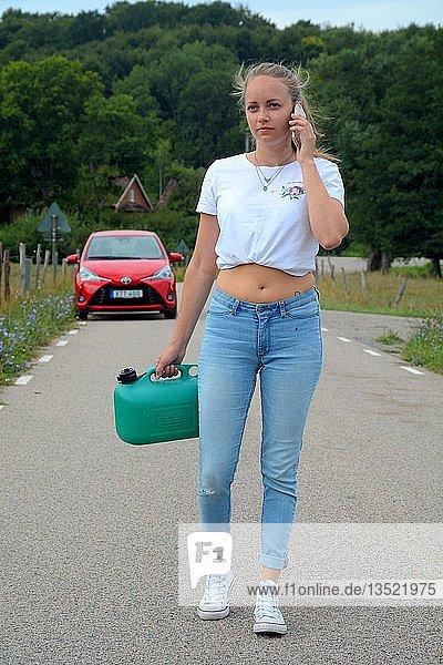 Autopanne  junge Frau mit Mobiltelefon und Benzinkanister vor liegen gebliebenem Auto  Scania  Schweden  Europa