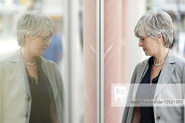 Woman  50 +  reflecting in a shop window