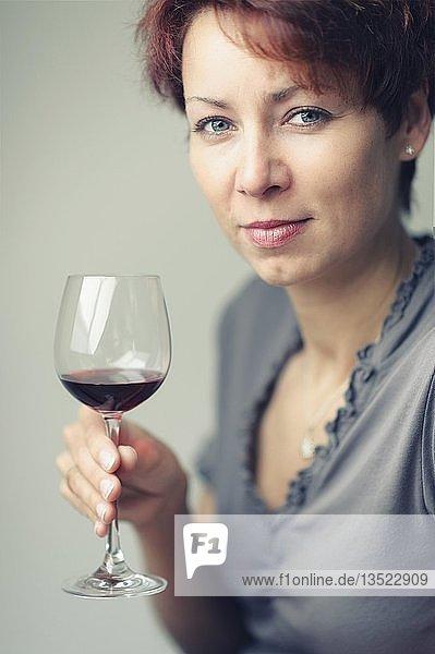Lächelnde junge Frau mit einem Glas Rotwein