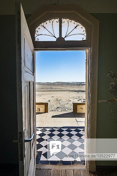 Blick durch eine Tür in die Wüste  alte Bergbaustadt Kolmanskop oder Coleman's Hill  bei Lüderitz  Namibia  Afrika
