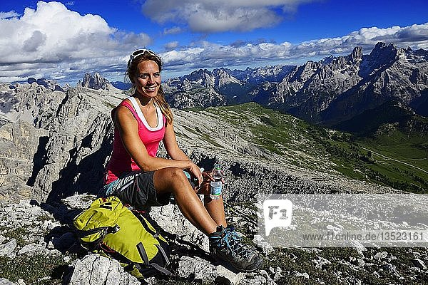 Young female hiker pauses during the ascent from the Prato Piazza to the summit of the Dürrenstein  in the background Monte Cristallo and the Three Peaks of Lavaredo  Sexten Dolomites  Hochpustertal  South Tyrol  Italy  Europe