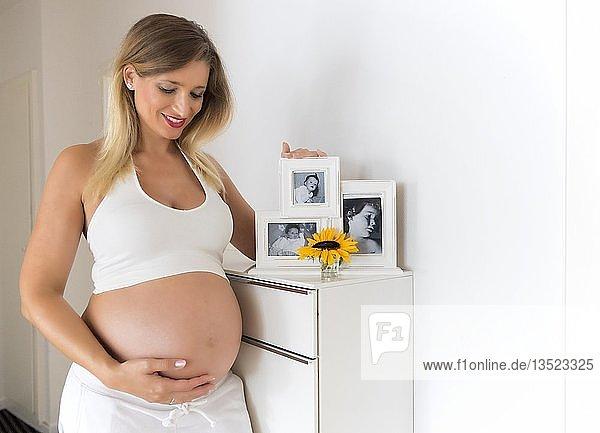 Frau im neunten Monat schwanger  posiert vor Babybildern mehrerer Generationen  Deutschland  Europa