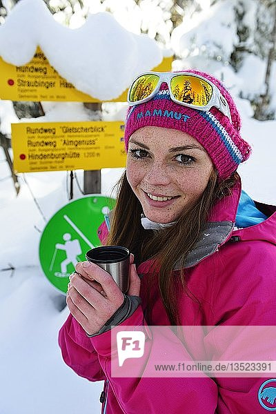 Frau im Winter bei der Rast mit Tee  Schneeschuhtour auf das Fellhorn  Reit im Winkl  Bayern  Oberbayern  Deutschland  Europa