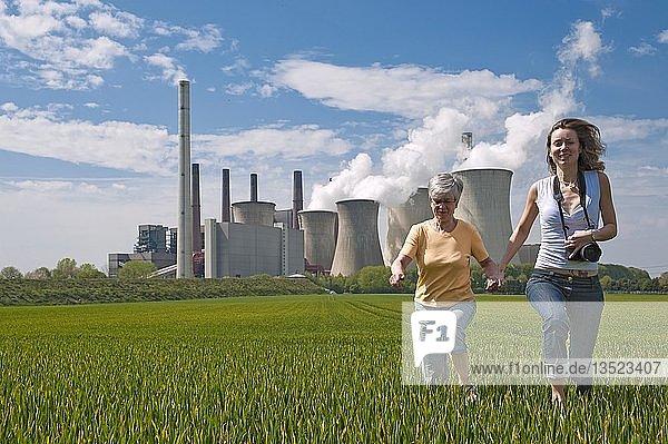 Zwei Frauen rennen durch ein Getreidefeld vor dem Kraftwerk Neurath  Grevenbroich  Rheinland  Nordrhein-Westfalen  Deutschland  Europa