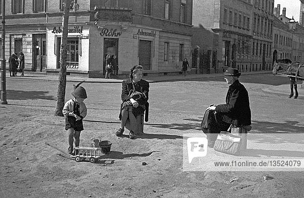 Zwei Frauen mit einem Kind unterhalten sich auf der Straße  1947  Leipzig  Sachsen  DDR  Deutschland  Europa