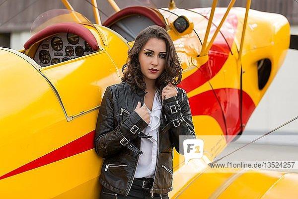 Junge Frau mit Lederjacke posiert mit gelben Doppeldecker Flieger  Fashion