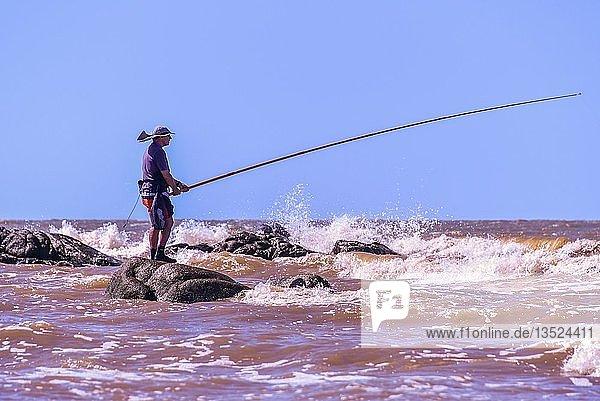 Angler in the surf of the Rio de la Plata  beach Rambla  Montevideo  Uruguay  South America