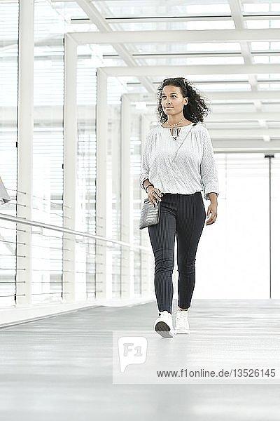 Junge Frau  geht durch Glastunnel  Deutschland  Europa