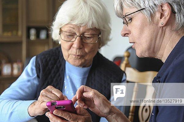 Zwei Seniorinnen mit einem Smartphone  Grevenbroich  Nordrhein-Westfalen  Deutschland  Europa