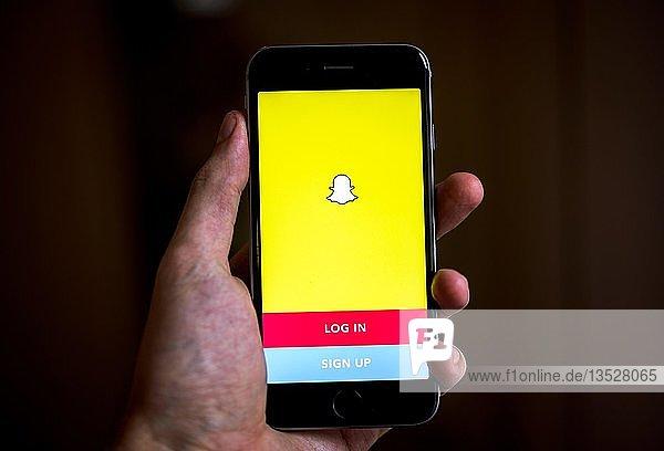 Hand hält iPhone mit Snapchat App  Login-Bildschirm  soziales Netzwerk  Instant Messenger  App-Icon  iPhone  iOS  Smartphone  Display  Deutschland  Europa