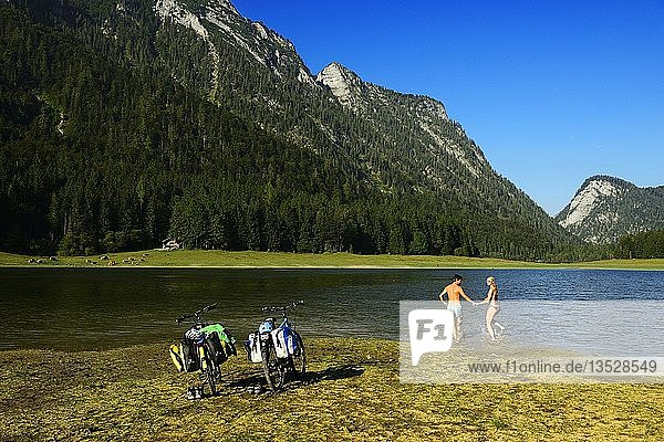 Two cyclists on the Mozart cycle path  swimming in the lake Mittersee  Ruhpolding  Chiemgau  Upper Bavaria